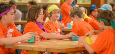 Group of children in orange tshirts and coloured buffs sitting at a camp table