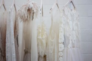 Close up images of white and light pink occasion dresses on clothing rack with white brick background