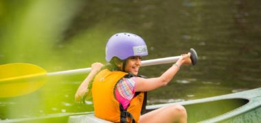 Image of smiling girl paddling a canoe in Cave Hill Creek
