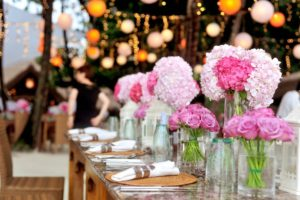 Close up image of pink floral arrangements on tables at a wedding