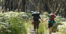 Image of two people with hiking bags walking in the bush